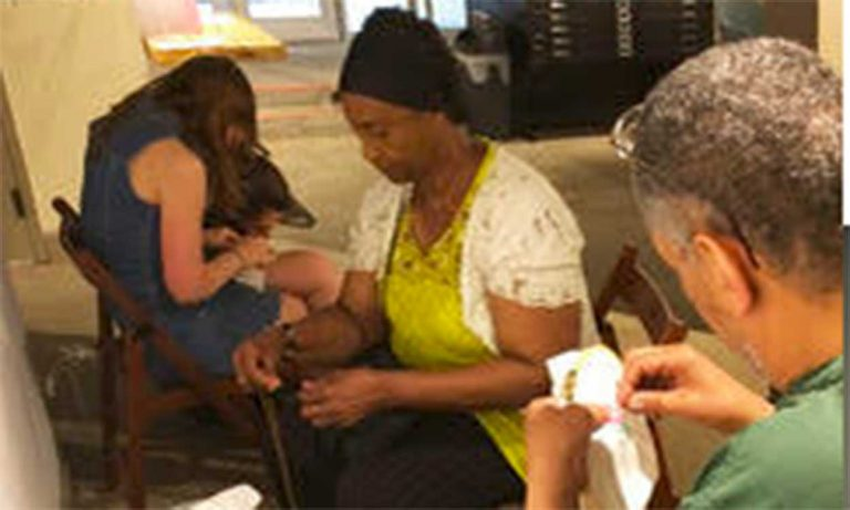 Photo of adult men and women embroidering